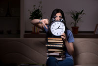 Young female student preparing for exams at night time