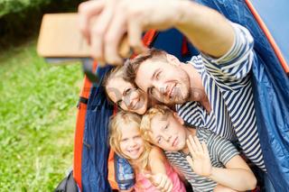Familie mit Kindern im Zelt macht ein Selfie