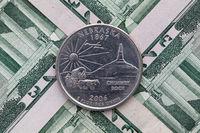 Symmetric composition of US dollar bills and a quarter of Nebraska.