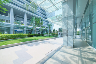 Exterior of a modern steel and green glass office building with empty walkway. panoramic and perspective view. modern architect design .
