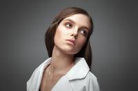 Portrait of a beautiful European fashion model on a gray background.