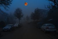 The blood moon in the dark night sky over a residential area.