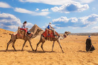 Tourists riding camels near the Pyramids of Giza