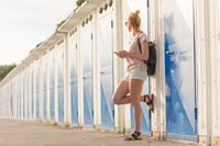 Blonde young female traveler wearing summer style clothing, holding mobile phone, against retro blue beach dressing rooms at summer time vacation.