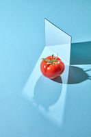 Composition from a mirror and a ripe tomato on a blue background with reflection of shadows and copy space. Organic vegetable