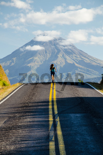 Running girl in green t-shirt on the road with mountain Taranaki in the background with clouds above, Egmont National Park, New Zealand, North Island