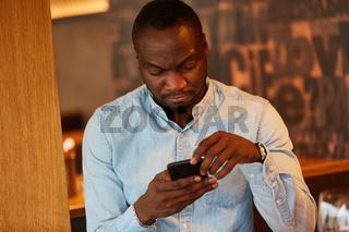 Afrikanischer Mann liest SMS auf dem Smartphone
