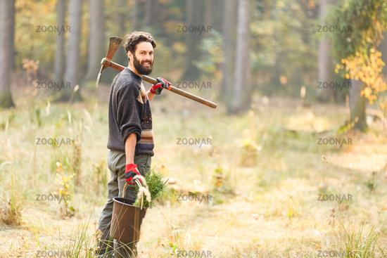 Junger Waldarbeiter oder Förster mit Kiefer Setzling