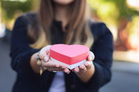 Female hands holding heart shaped gift box.
