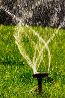 Lawn sprinkler agricultural system working. Blurred water fly in the air
