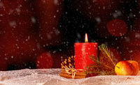 Candle with christmas decoration and snow