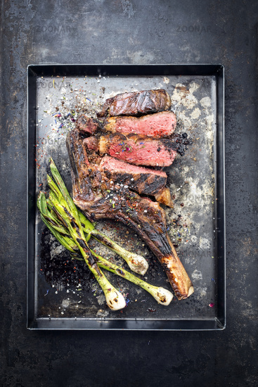 Barbecue dry aged wagyu tomahawk steak with leek as top view on a black metal sheet