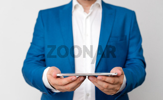 Man in the blue suite and white shirt holds mobile phone in the hand. Business concept with businessman and mobile phone in the hand.