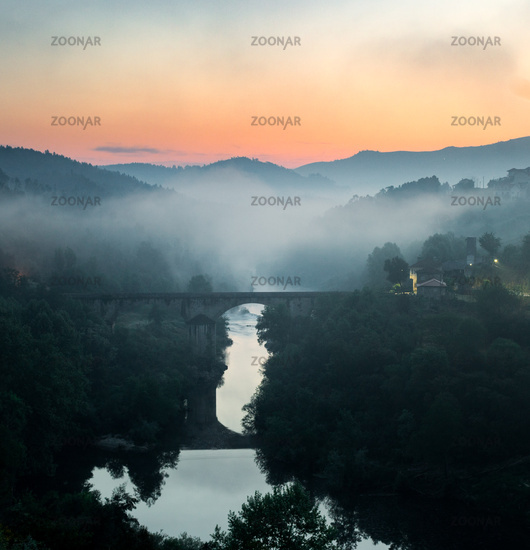 Mist is formed along a river valley during a sunrise with a bridge in the foreground.