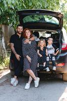 Happy family posing on camera near the car