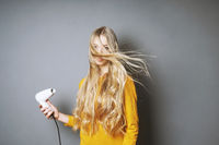 young blond woman blow-drying her hair