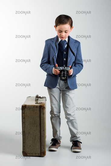 Young boy dressed up with photo camera and suitcase