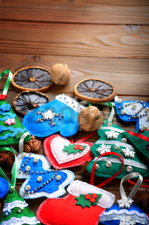 Assorted handmade rustic felt Christmas tree decorations with anise cinnamon and walnuts on wooden table