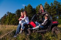 group of young people driving a off road buggy car