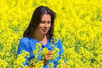 Woman looks at flower in yellow rapeseed field