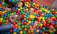 parents and kids playing in the pool with colorful balls