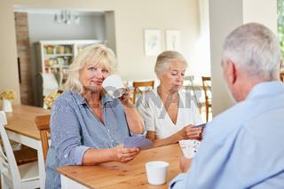 Senioren im Altenheim spielen Karten zusammen