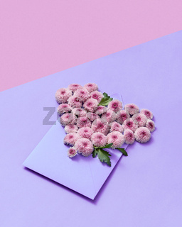 Handmade envelope with flowers heart on a duotone pastel background.