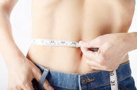 Caucasian female model in blue jeans with tape measure showing her flat stomach. Healthy lifestyle and Weightloss concept.