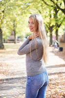 rear view of young woman wearing jeans and sweater turning head around