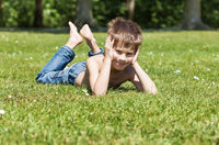 blond boy lying on grass