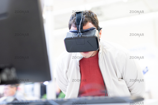Young man wearing virtual reality headset and gesturing while sitting at his desk in creative office