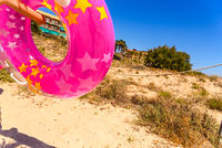 Inflatable round float of pink childish colors on the way to the beach.