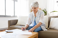 senior woman with papers and calculator at home
