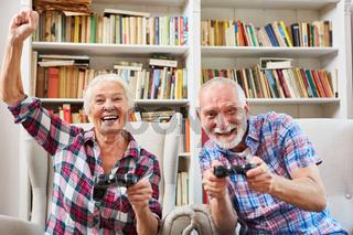Paar Senioren spielt Videospiel mit Konsole im Wohnzimmer
