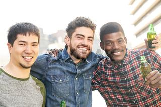 Junge multikulturelle Freunde feiern mit Bier