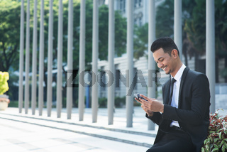 Businessman using mobile phone outdoor