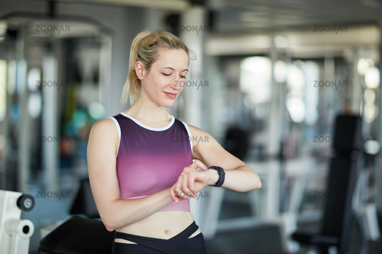 Frau schaut auf Wearable Smart Watch beim Training