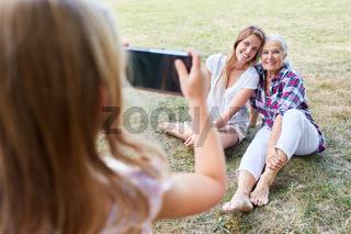 Kleines Mädchen fotografiert Oma und Mutter
