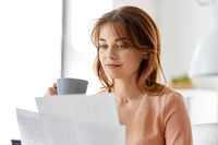 businesswoman with papers drinks coffee at office