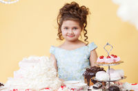 Pretty smiling girl posing at table with desserts