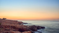 Colorful orange sunset over a rocky coastline