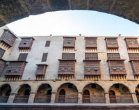Facade of caravansary of Bazaraa framed by stone arch, with vaulted arcades and wooden oriel windows, Cairo, Egypt