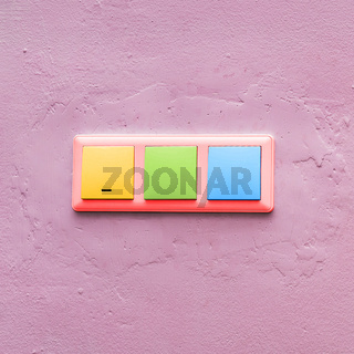 Multi-colored light switches on a pink wall. Fashionable colorful electrical switch. Creative style. Concept art
