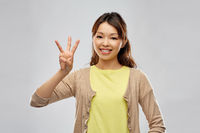 smiling asian woman showing three fingers