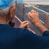 Old fisherman repairs fishing net
