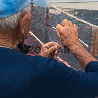 Old fisherman repairs fishing net