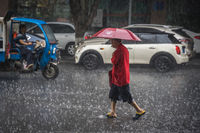 Man walking in tropical monsoon rain