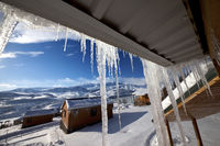 Roof with big sunlit icicles and small wooden houses at snowy winter mountains