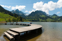 Schwarzsee, FR / Switzerland - 1 June 2019: two men best friends enjoy the summer lakeside view at t