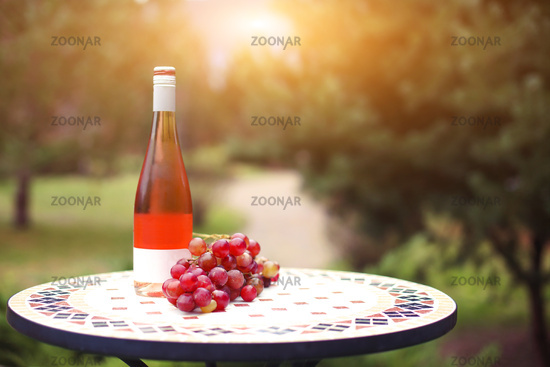 One bottle of rose wine in autumn vineyard on marble table.
